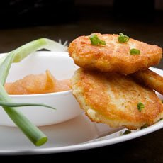 Latkes with Apple Sauce and Green Onion on a white plate