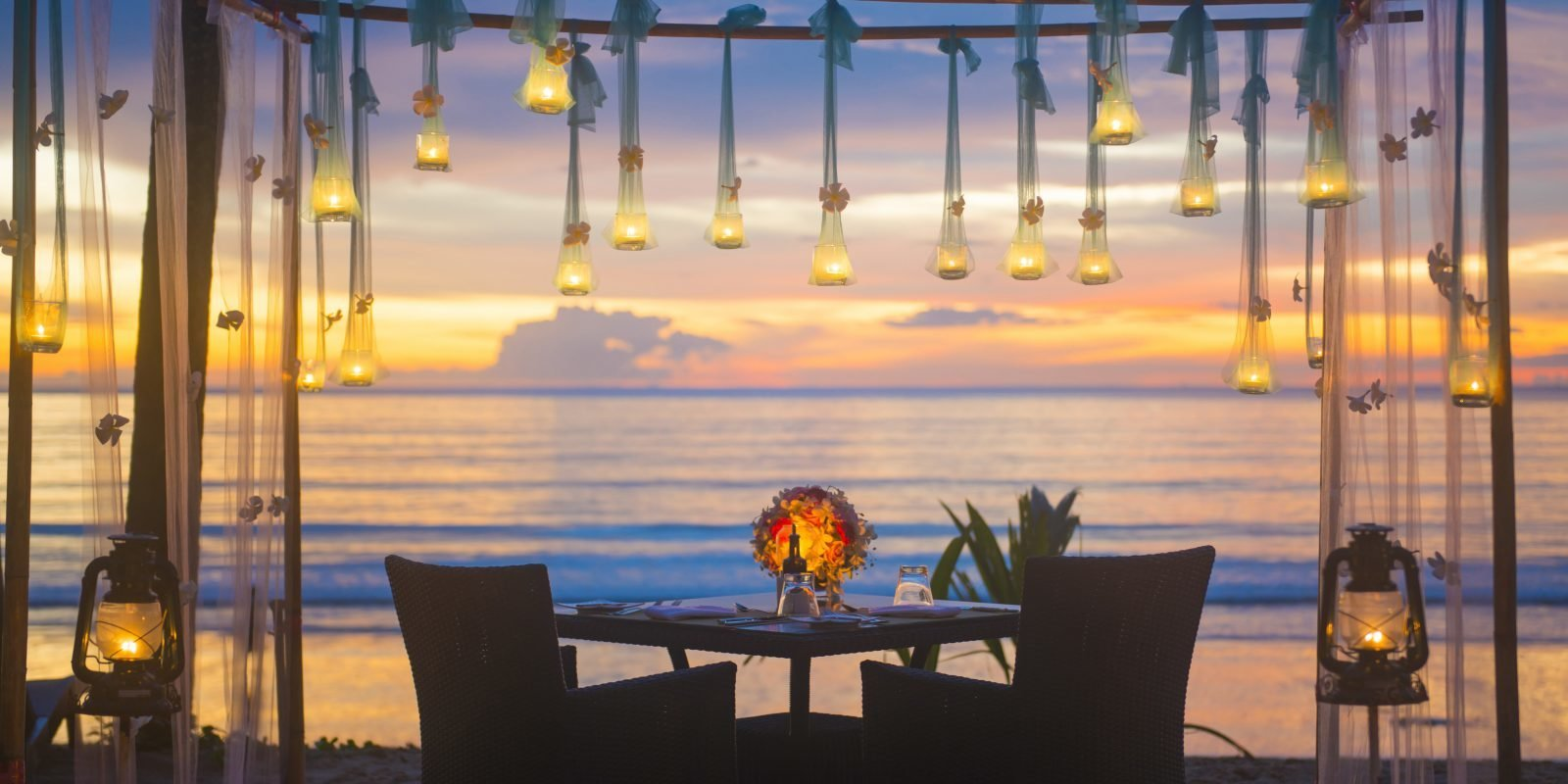 romantic dinner setup on the beach, sunset